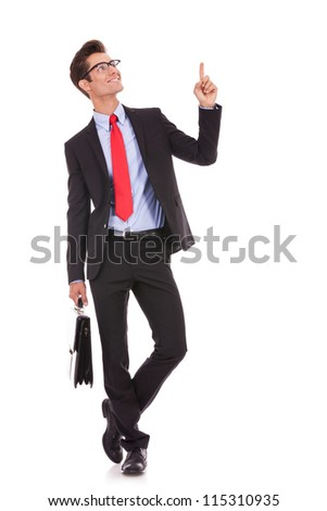 Handsome young business man happy smile pointing finger up to empty copy space, while holding a briefcase - stock photo