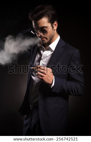 Handsome young business man holding a cigarette in his hand while blowing smoke. - stock photo