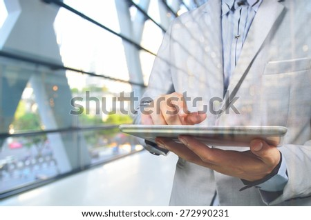 Handsome Young Business Man in Office Building using Digital Mobile Tablet.  Selective focus on Tablet in Hand. - stock photo