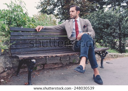 Handsome young  business man in the park after work, vintage style, retro filtered look - stock photo