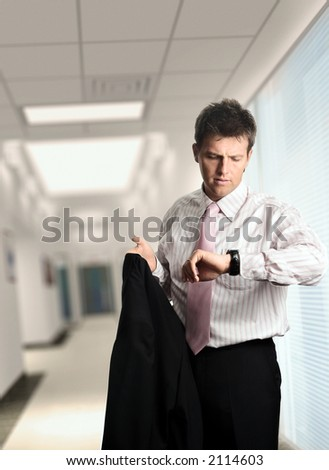 Handsome young business man is looking at his watch while he leaves the modern office.