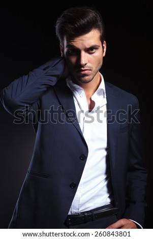Handsome young business man looking at the camera while holding one hand to his neck.