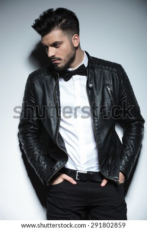 Handsome young business man looking down while holding both hands in his pockets. - stock photo