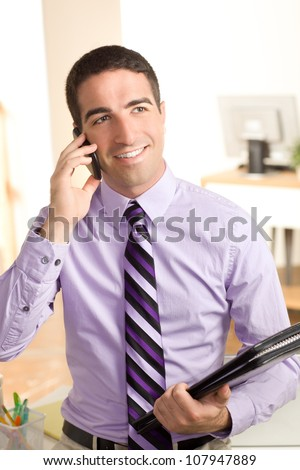 Handsome young business man on phone looking off holding a leather pad in an office setting - stock photo