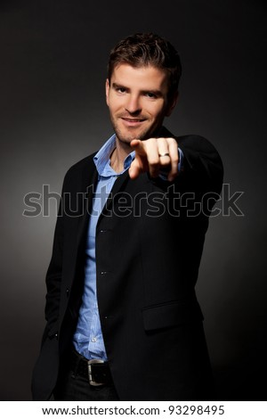 Handsome young business man points finger at you - stock photo