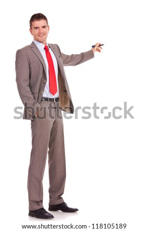 handsome young business man presenting something in the back with a pen and holding a hand in his pocket while looking at the camera on white background - stock photo