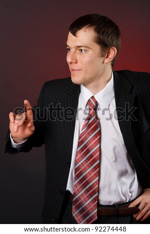 Handsome young business man standing on black background - stock photo