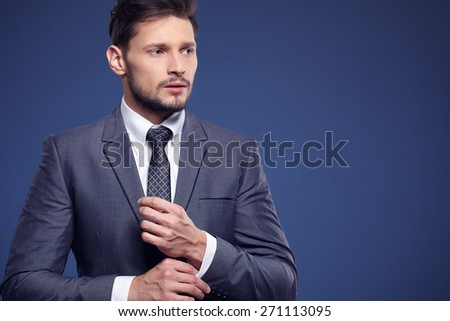 Handsome young business man standing on blue background - stock photo