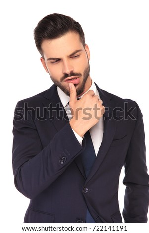 handsome young business man touching lips with his thumb and looks to side on white background