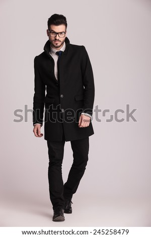 Handsome young business man wearing a long black coat walking towards the camera. - stock photo