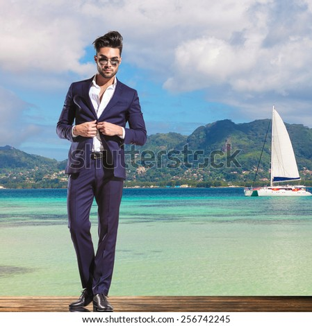 handsome young business man wearing sunglasses is unbuttoning his suit while standing on a deck on the shore of the sea, little boat sailing in the background - stock photo