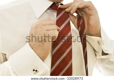 Handsome young businessman adjusting tie