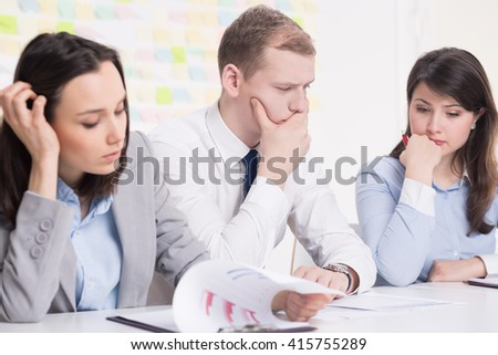 Handsome young businessman and his two female colleagues working on new business plan