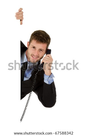 Handsome young businessman behind wall holding telephone receiver. Having a conversation. Copy space. Studio shot. White background. - stock photo