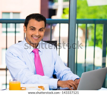 Handsome young businessman eating healthy breakfast, coffee, juice and working on laptop, isolated on a city background