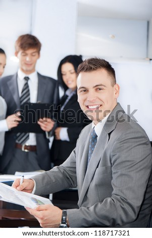 handsome young businessman happy smile. Sitting at the desk at office with group of business colleagues people in the background businesspeople working in team at meeting, man looking at camera