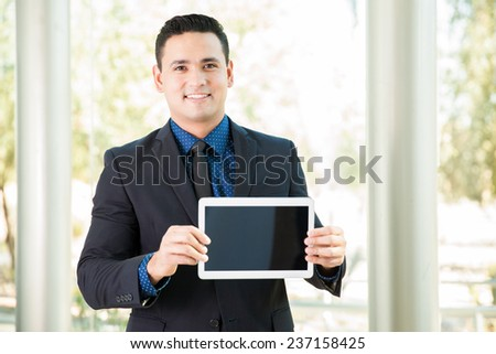 Handsome young businessman holding a tablet computer and showing its screen