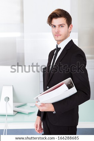 Handsome Young Businessman Holding Folder In Office