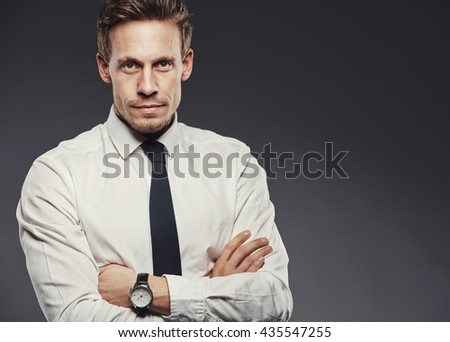Handsome young businessman in a shirt and tie looking focused, standing with arms crossed against a gray background - stock photo