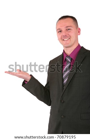 Handsome young businessman in a suit presenting something with a smile