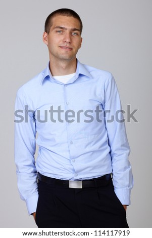 Handsome young businessman in blue shirt standing with hands in pocket, isolated on grey