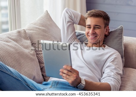 Handsome young businessman in casual clothes is using a digital tablet and smiling while lying on sofa at home - stock photo
