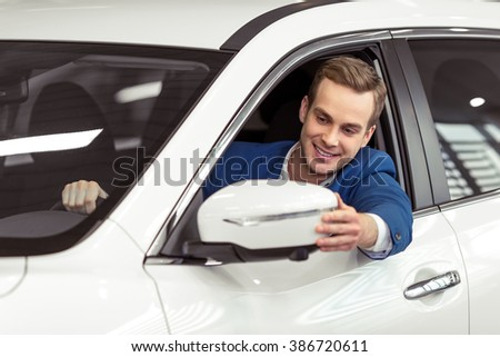 Handsome young businessman in classic blue suit is smiling and looking in the side mirror while sitting in car in a motor show - stock photo