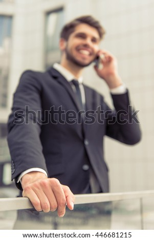 Handsome young businessman in classic suit is talking on the mobile phone and smiling, standing outdoors. Focus on his hand on balcony balustrade - stock photo