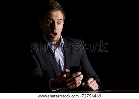 Handsome young businessman in dark suit sitting at office desk being surprised about text messages on mobile-phone, low-key image isolated on black background. - stock photo
