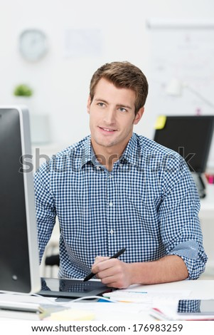 Handsome young businessman in shirtsleeves sitting working at his desktop computer using a tablet and stylus to navigate