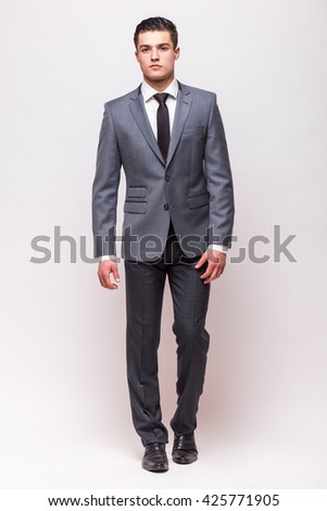 Handsome young businessman  in suit standing against white background - stock photo