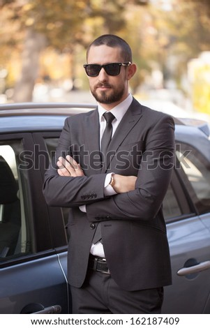 Handsome young businessman in suit standing near car