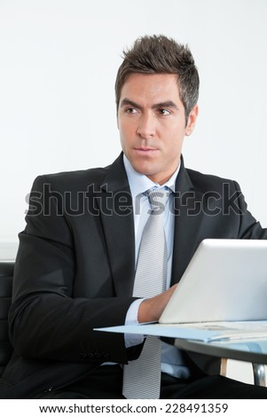 Handsome young businessman in suit using digital tablet at desk in office