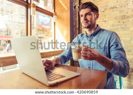 Handsome young businessman is using a laptop, holding a cup of hot drink and smiling while working in the cafe - stock photo