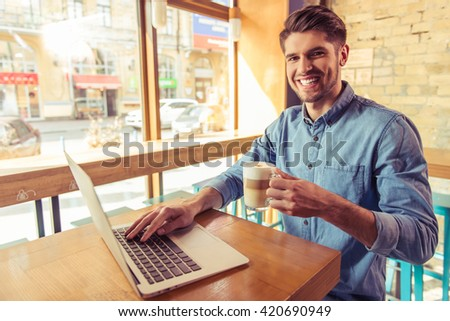 Handsome young businessman is using a laptop, holding a cup of hot drink, looking at camera and smiling while working in the cafe - stock photo