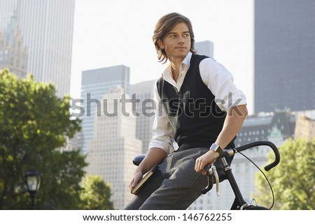 Handsome young businessman leaning on bicycle in city park - stock photo