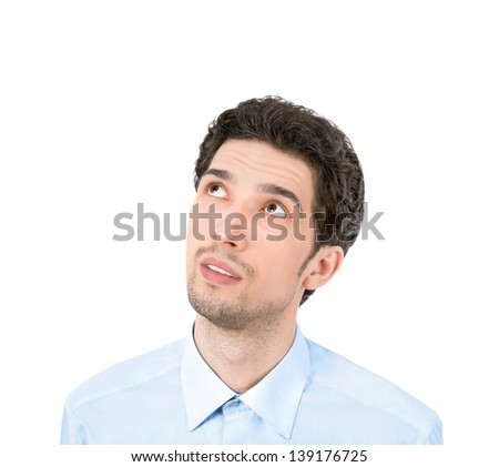 Handsome young businessman looking up at copyspace. Isolated on white background - stock photo