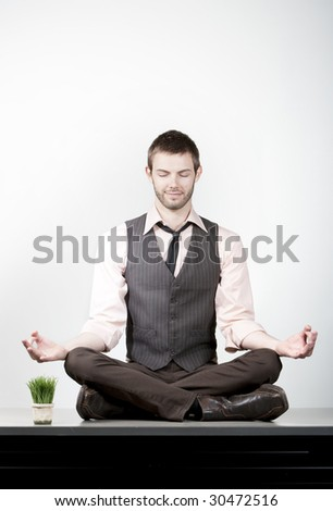 Handsome young businessman meditating on office desk - stock photo