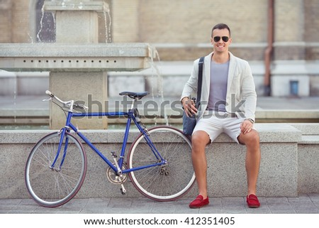 Handsome young businessman or student is sitting near the fountain in city centre with his bicycle beside him