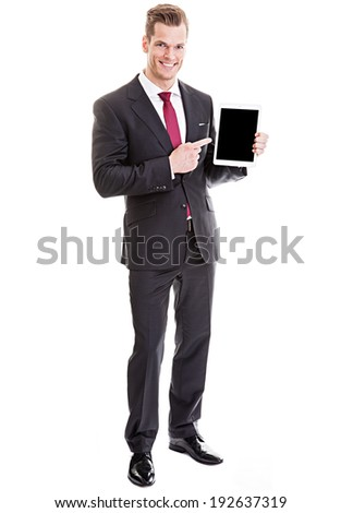 Handsome young businessman pointing at modern tablet computer - full length portrait, isolated on white
