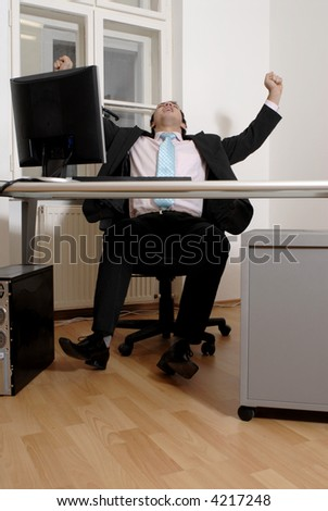 Handsome young businessman raise hands to show success at the desk in office.