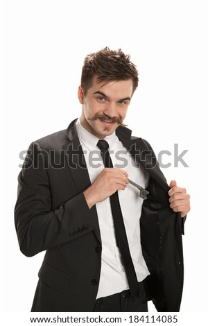 Handsome young businessman retrieves a skeleton key from his lapel pocket, isolated on white background - stock photo