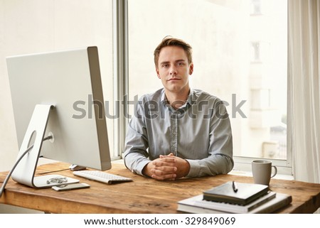 Handsome young businessman sitting at his desk in a calm and confident position and looking steadily at the camera - stock photo