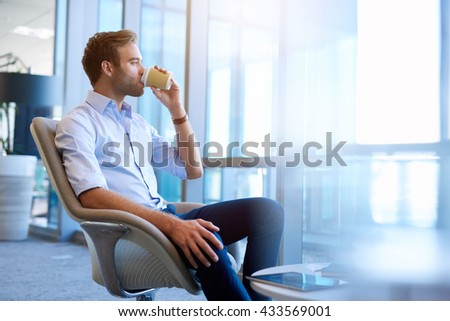 Handsome young businessman sitting comfortably in a modern office, sipping his takeaway coffee and looking out of the window - stock photo