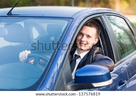 Handsome young businessman sitting in his new car - stock photo