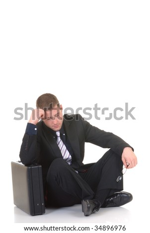 Handsome young businessman, sitting next to  briefcase, troubled pensive look, studio shot. - stock photo