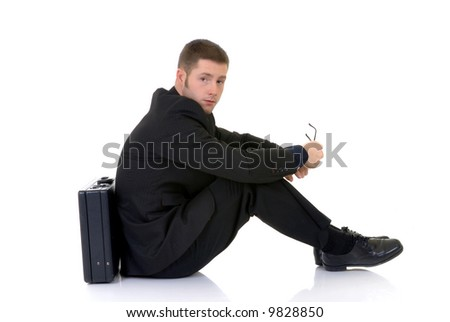 Handsome young businessman, sitting next to  briefcase, troubled pensive look, studio shot.