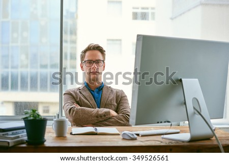 Handsome young businessman sitting with his arms folded at his desk and staring seriously at the camera in a bright contemporary office space - stock photo