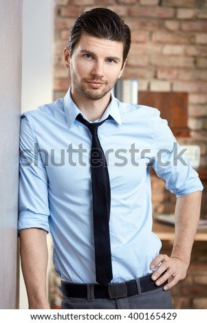 Handsome young businessman standing against wall with hand on hip. - stock photo