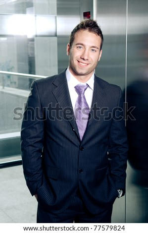 Handsome young businessman standing in elevator - stock photo